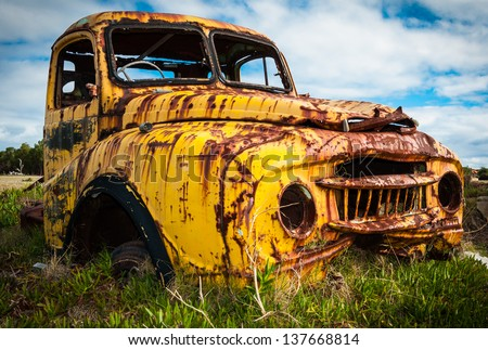 Abandoned yellow pickup truck rusting in a field. - stock photo