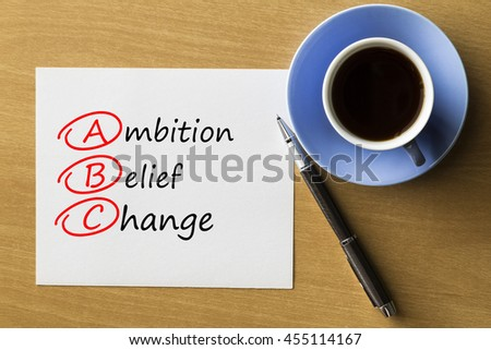 ABC Ambition Belief Change - handwriting on notebook with cup of coffee and pen, acronym business concept