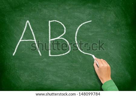 ABC, education and primary school blackboard concept. School teacher writing ABC alphabet in English class or preschool.on chalkboard. - stock photo