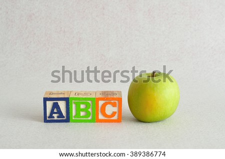 ABC with colorful alphabet blocks isolated against a white background with a green apple - stock photo