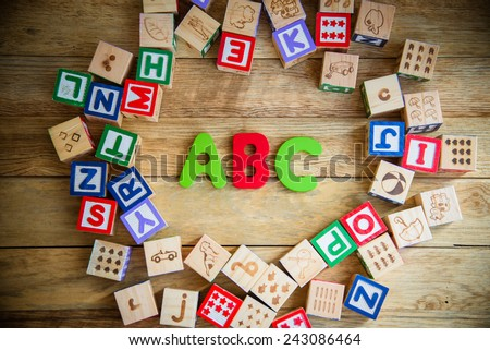ABC word in wooden block alphabet lay on wooden floor in circle shape - stock photo