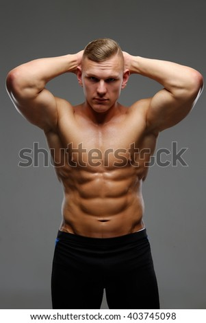 Abdominal shirtless man isolated on a grey background.