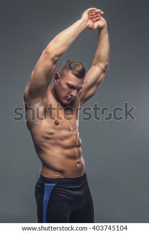 Abdominal shirtless man isolated on a grey background. - stock photo