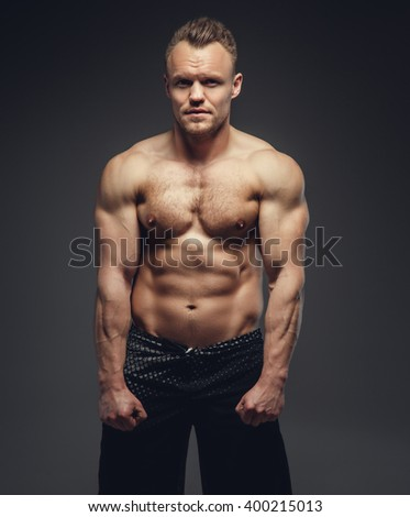 Abdominal shirtless muscular guy isolated on a grey background.