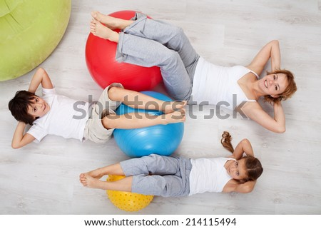 Abdominal workout - woman and kids doing gymnastic exercises, top view - stock photo