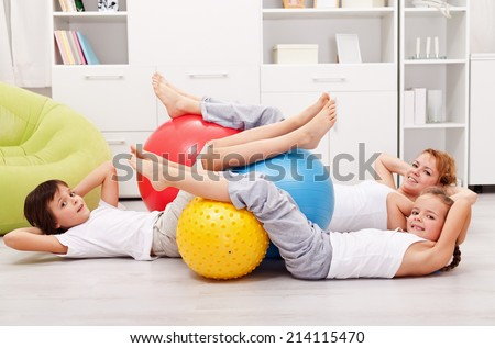 Abdominal workout - woman with kids doing gymnastic exercises - stock photo