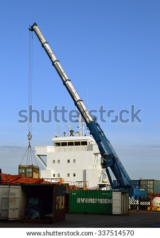 ABERDEEN, SCOTLAND - 21 OCTOBER, 2015: A crane loads containers onto a ship in Aberdeen Harbour, Scotland