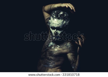 Aboriginal, wild man with white painted face and full body black paint - stock photo