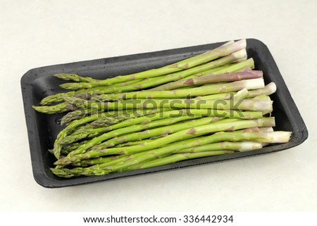 About one pound of raw green asparagus spears in a black plastic packaging tray on a kitchen counter. Uncooked asparagus spears in a black plastic tray on a countertop