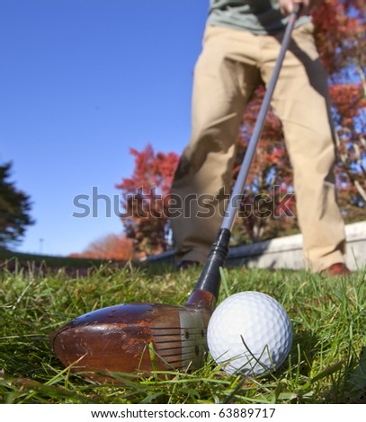 About to hit a fairway wood with an old, traditional wood club on a beautiful fall day.