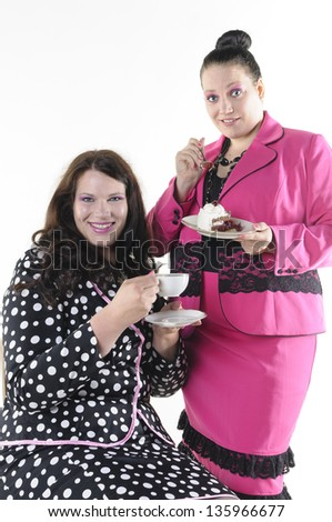 About two faithfully models wear flashy costumes and chat over coffee and cake, isolated against white background.