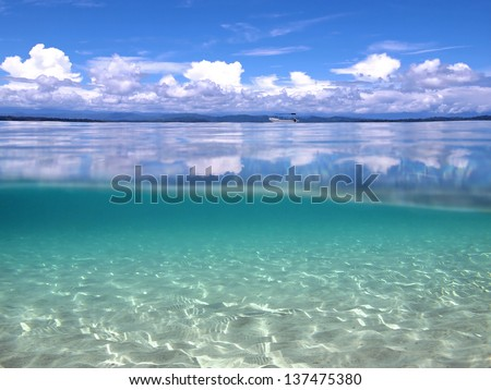 Above and below waterline in the Caribbean sea with clouds reflected on water surface and sandy seabed underwater - stock photo