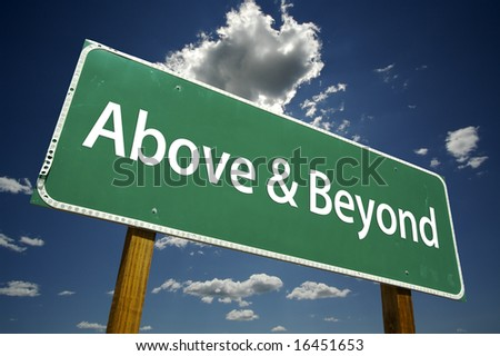 Above and Beyond Road Sign with dramatic clouds and sky. - stock photo
