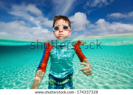 Above and underwater photo of cute little boy swimming in ocean  - stock photo