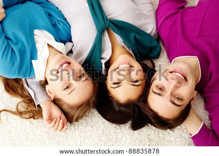 Above angle of attractive friends looking at camera and smiling - stock photo