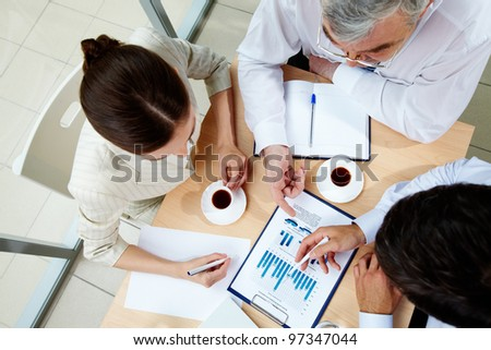 Above angle of business team discussing business documents at meeting - stock photo