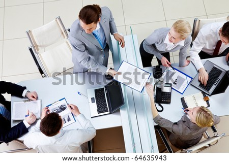Above angle of confident man passing contract to pretty secretary in working environment