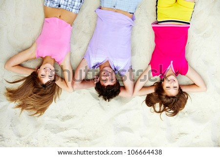 Above angle of laughing teenage friends lying on sandy beach - stock photo