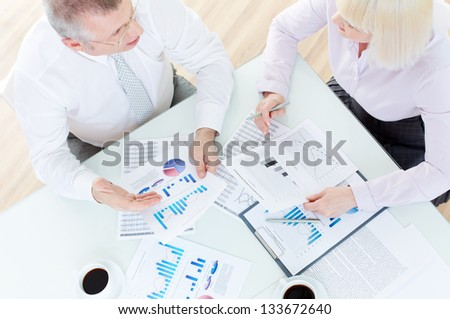Above angle of mature business partners discussing papers at meeting