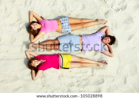 Above angle of relaxed teenage friends lying on sandy beach