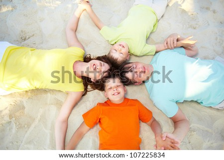 Above angle of serene family lying on sand on summer