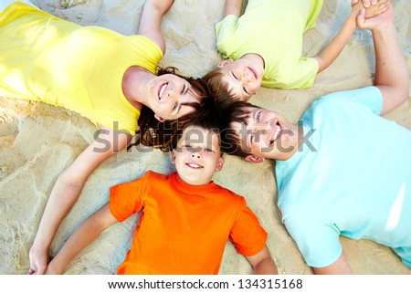 Above angle of serene family lying on sand on summer - stock photo