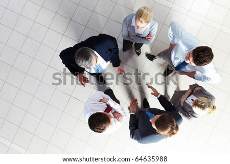 Above angle of several smart associates talking to each other at meeting - stock photo