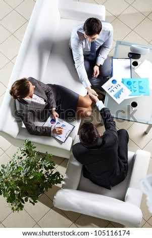 Above angle of successful associates making agreement at meeting - stock photo