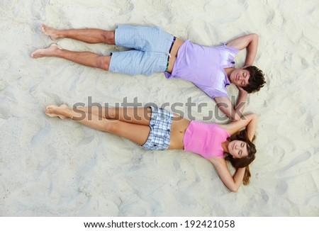 Above angle of teenage couple having rest on sandy beach - stock photo