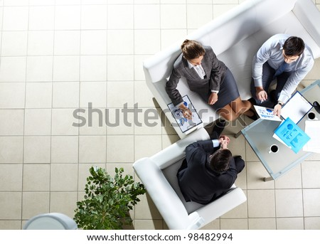Above angle of three associates interacting at meeting - stock photo