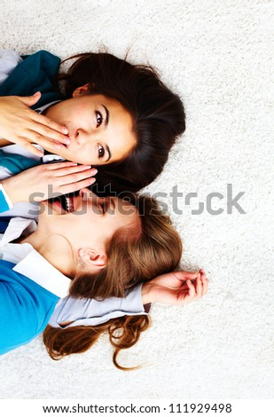 Above angle of two girls gossiping - stock photo