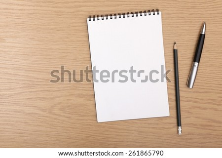 Above. Blank notepad with pen and pencil on office wooden table - stock photo
