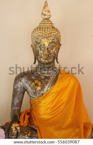 above body part of sitting ancient buddha statue filled with gold leaf, one of the most important and visiting historical landmark at ayutthaya, Thailand for tourism