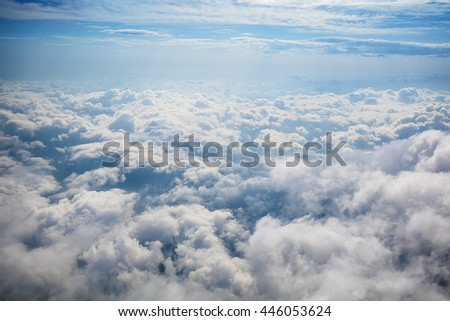 Above clouds, sky as seen in window of an aircraft - stock photo