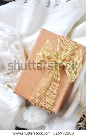 Above of golden gift box on white scarf