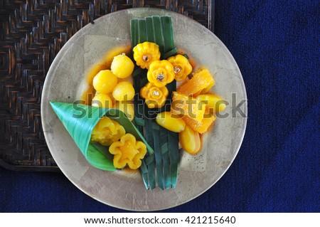 Above of golden Thai dessert plate on blue background - stock photo