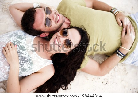 Above shot of a young couple in love in a tropical beach. Shot from above.  - stock photo