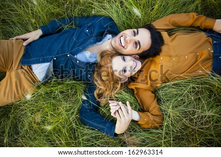 Above shot of a young couple in the countryside lying in the grass - stock photo