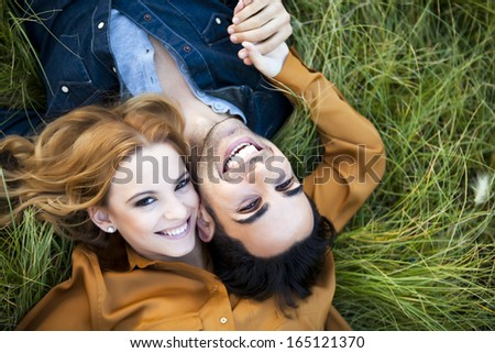 Above shot of a young couple in the countryside. She is kissing his cheek - stock photo