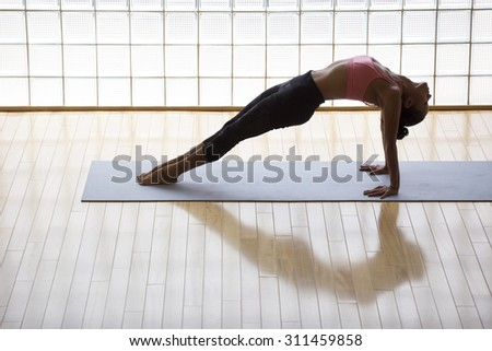 Above shot of a young woman practicing in a yoga studio. Thsi is called reverse plank pose, its a heart opener pose. - stock photo
