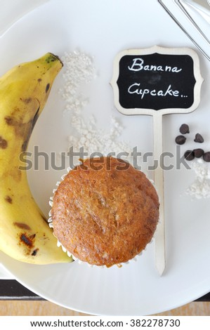 Above shot of banana cupcake with sign on white plate - stock photo