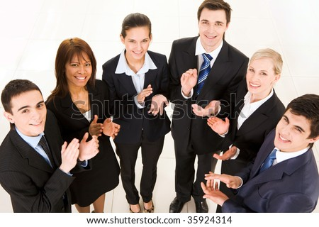 Above shot of happy business partners applauding and looking at camera - stock photo