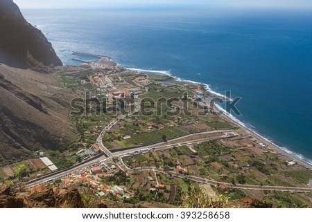 Above the headland of the Valle Gran Rey on the Canary Island La Gomera. View to the small villages at the end of the canyon. Vueltas, La Puntilla, Borbalan. Also the harbor, situated in Vueltas - stock photo