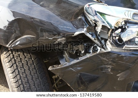 Above the headlights and wheels, flat tires deflated due to an accident. - stock photo