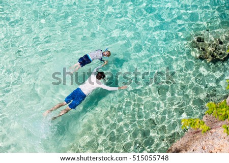above view at family of two snorkeling at anguilla enjoying caribbean sea, active lifestyle concept