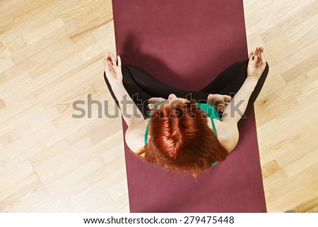 Above view at lotus yoga pose taken by caucasian redhead woman wearing green shirt - stock photo