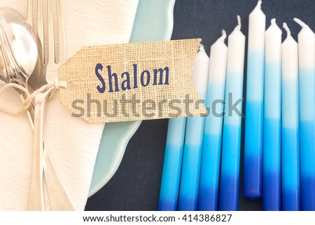 Above View Closeup of Hanukkah Table Place Setting with Candles, Plates, Silverware, Napkin and Shalom Name Tag with Room or Space for your words, text, or copy over blur candles. Horizontal warm tone