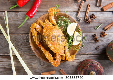 Above view cooked delicious hot and spicy sauce blue crab and ingredients, on wooden background. Fresh cook with hot smoke steams. - stock photo