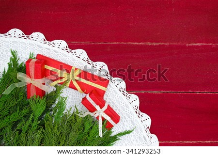 Above view looking down from Christmas tree at  tree skirt and holiday presents on antique rustic wood background