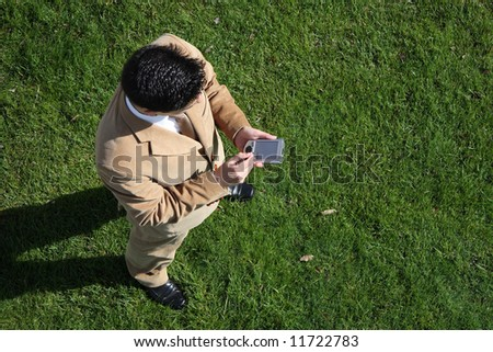 Above view of a business man looking to a pocket PC - stock photo